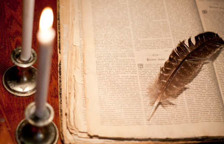 candelabrum: Candles in the dark near book and feather on the table