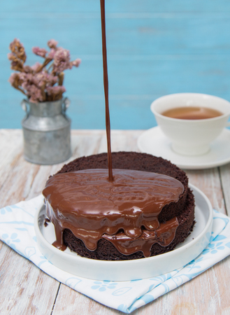 cake topping: Chocolate syrup being poured over a cake,topping chocolate fudge on cake