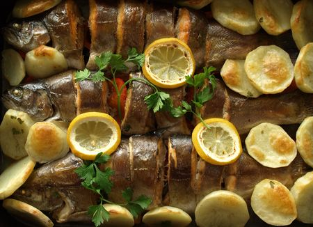 trout fried on a grill with potato and lemon photo