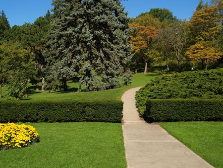 Garden with paved path and blooming flowers at the beginning of the autumn photo