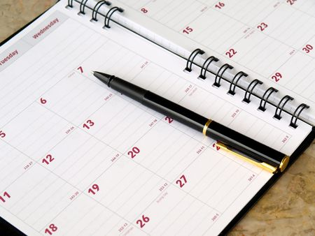 organizer: monthly planner with pen on the table            Stock Photo