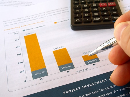 Male hand with pen on the project investment chart with calculator