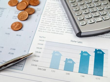 stock quotes: Pen, coins and calculator on the home sales chart         Stock Photo