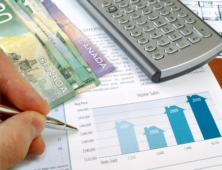 Male hand with pen on the investment chart with calculator and canadian dollars