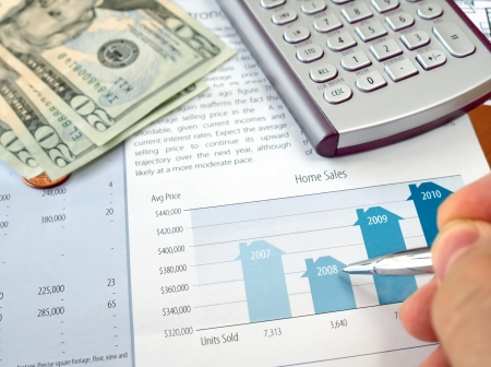 Male hand with pen on the investment chart with calculator and dollars