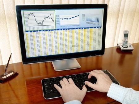 Mannelijke handen op het toetsenbord in de voorkant van de computerscherm met financiële gegevens en grafieken      Stockfoto