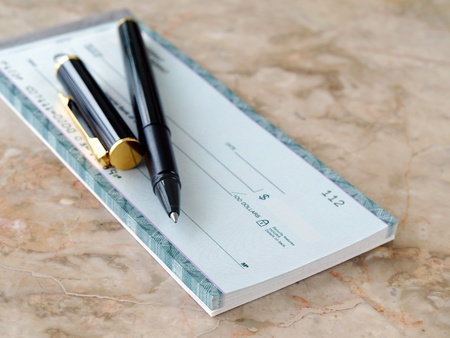Blank cheque with pen on the table         Stock Photo