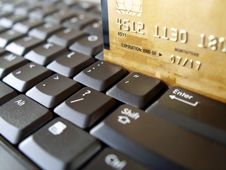 purchasing: Golden credit card on computer keyboard.