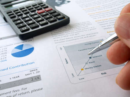 Male hand with pen on the investment chart with calculator   photo