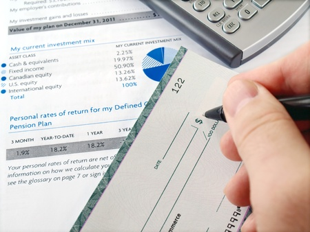 pension fund: Man filling out  cheque on the investment papers      Stock Photo