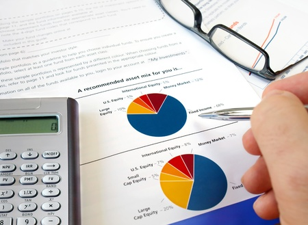 Male hand with pen on the pie investment chart with calculator and glasses    Stock Photo