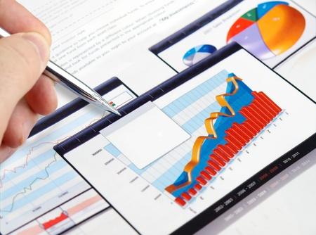 Mannenhand met pen op de grafieken van de investeringen