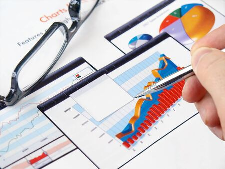 Male hand with pen on the investment charts with glasses