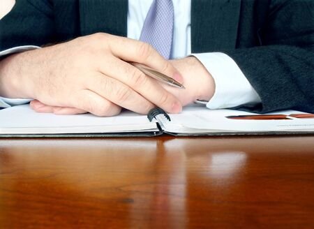 Close-up of male hands with pen at the business meeting.
