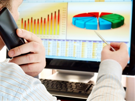 analytics: Man on a phone analyzing financial data and charts on computer screen. Stock Photo