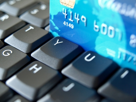 order online: Credit card on computer keyboard. Stock Photo
