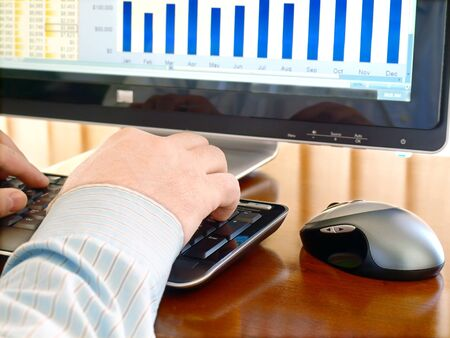 Male hands on the keyboard in front of computer screen with charts photo