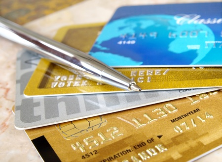 Silver pen on the pile of credit cards .