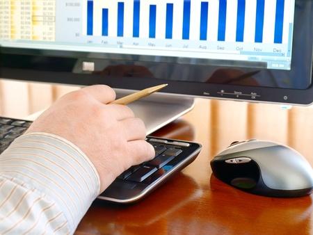 Mannenhand met pen op het toetsenbord in de voorkant van de computerscherm met grafieken Stockfoto