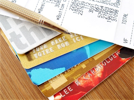 Pile of credit cards with pen and receipt.