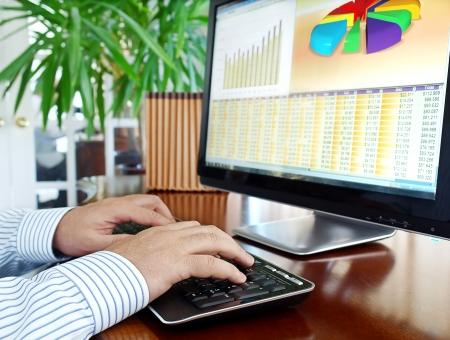 monitor de computadora: Manos de los hombres en el teclado en la parte frontal de la pantalla del ordenador con los datos financieros y cuadros