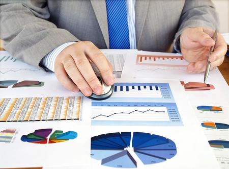 fondos negocios: Empresario analizar gr�ficos de inversi�n en su lugar de trabajo Foto de archivo