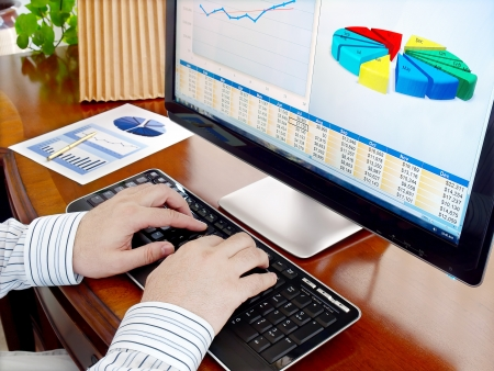 Male hands on the keyboard in front of computer screen with financial data and charts Stok Fotoğraf - 10098742