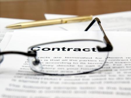 firmando: Gafas de lectura en documentos y la palabra contrato en foco Foto de archivo