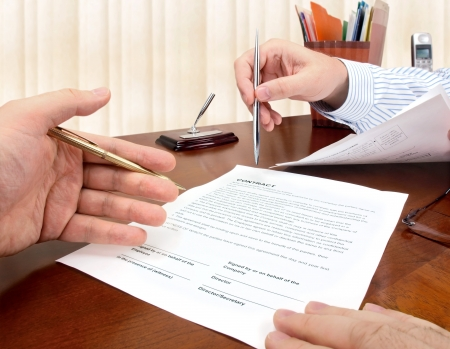 Male hands with pens signing a contract.