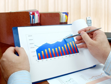 Male hand with pen on the investment chart.