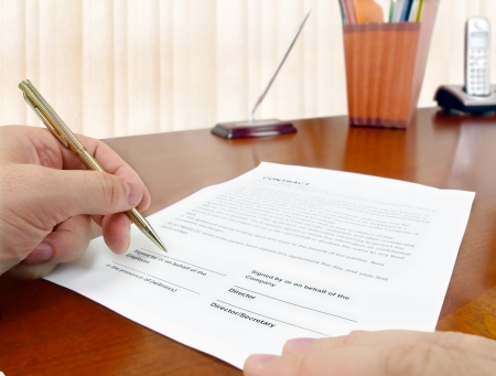 signing contract: Male hand with pen signing a contract.