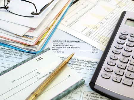 A pile of bills, checkbook, pen and calculator on the table.  photo