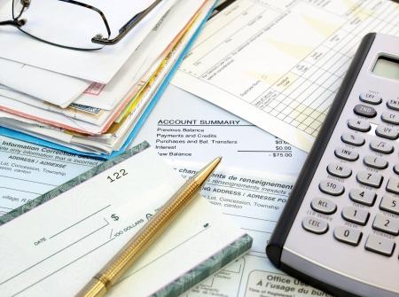 dichiarazione: Una pila di bollette, libretto degli assegni, penna e calcolatrice sul tavolo.