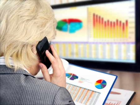 investors: Woman on a phone analyzing financial data and charts . Stock Photo