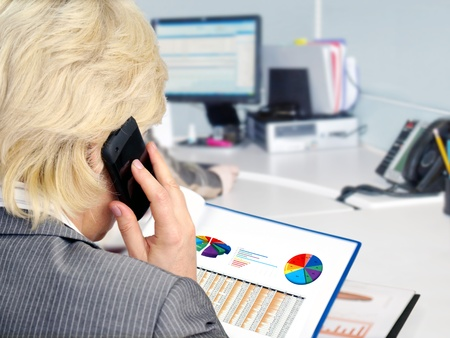 analyzing: Woman on a phone analyzing financial data and charts . Stock Photo