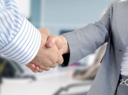 Closeup of businessmen and businesswoman shaking hands.