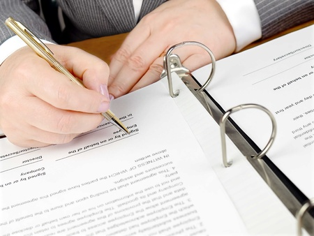 business sign: Female hand with pen signing a contract.  Stock Photo