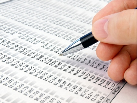Male hand with pen analyzing  financial data.