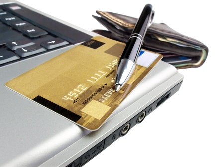 Credit card with pen on laptop ready for online purchase. Isolated. 版權商用圖片