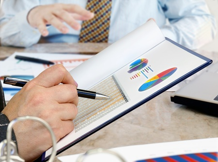 business results: Closeup of hands with financial  charts  at business meeting in the office. Stock Photo