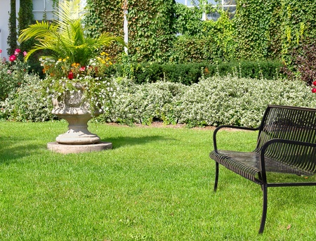 Sunny day in garden with bench and flowers in  sculptural stone planter  photo