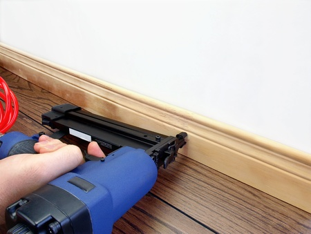 Male hand with carpenter tool installing baseboard