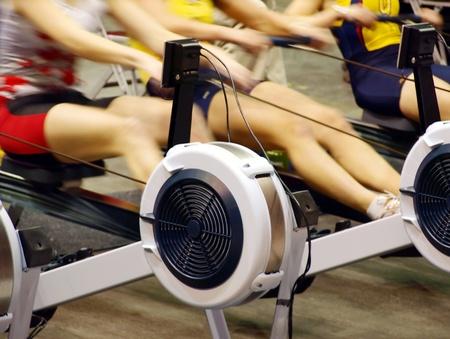 m�quina: Las ni�as el ejercicio en el gimnasio en las m�quinas de remo Foto de archivo