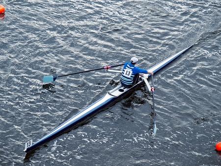 ロウイングのレガッタの間にボートで単一男