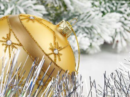 Golden Christmas ball on the snow-laden trees background   免版税图像