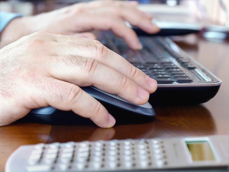 Male hands using a computer mouse and keyboard  photo