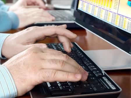 mecanograf�a: Manos de los hombres en el teclado en la parte frontal de la pantalla del ordenador con gr�ficos