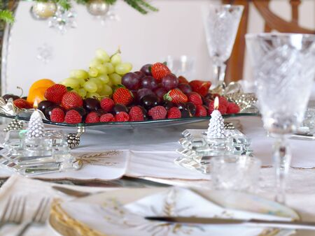 Holiday place setting with fruit tray and candles photo