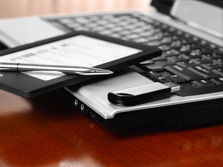 office desk: Home office with laptop, pen, phone and USB stick