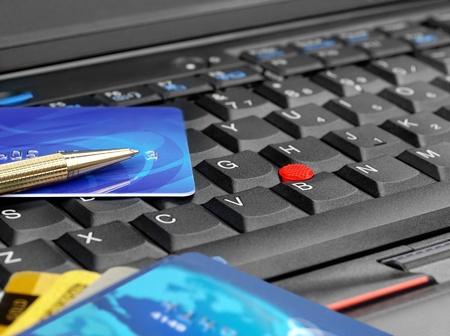 mastercard: Credit cards and pen on computer keyboard Stock Photo
